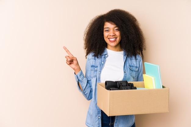 Jovem mulher afro, movendo-se para casa.