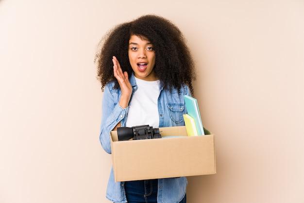 Jovem mulher afro, mudando para casa isolada jovem mulher afro surpresa e chocada.
