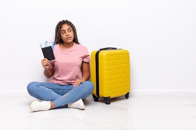 Jovem mulher afro na vista de perfil, olhando para copiar o espaço à frente, pensando, imaginando ou sonhando acordado. conceito de férias