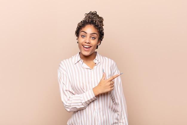 Jovem mulher afro parecendo animada e surpresa, apontando para o lado e para cima para copiar o espaço