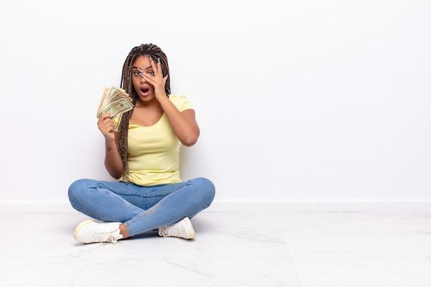 Jovem mulher afro parecendo chocada, assustada ou apavorada, cobrindo o rosto com a mão e espiando por entre os dedos. conceito de dinheiro