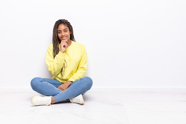 Jovem mulher afro parecendo feliz e sorrindo com a mão no queixo, pensando ou fazendo uma pergunta, comparando opções