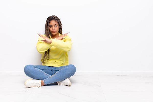 Jovem mulher afro parecendo irritada e cansada de sua atitude, dizendo chega! mãos cruzadas na frente, dizendo para você parar