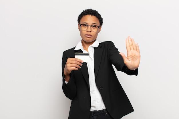 Jovem mulher afro parecendo séria, severa, descontente e irritada mostrando a palma da mão aberta fazendo gesto de pare