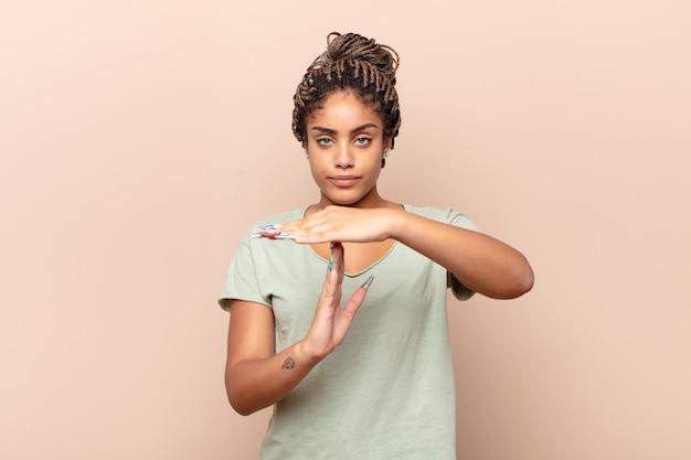 Jovem mulher afro parecendo séria, severa, irritada e descontente, fazendo sinal de castigo