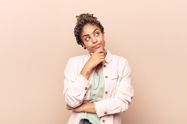 Jovem mulher afro pensando, pensando ou imaginando ideias, sonhando acordada e olhando para cima para copiar o espaço