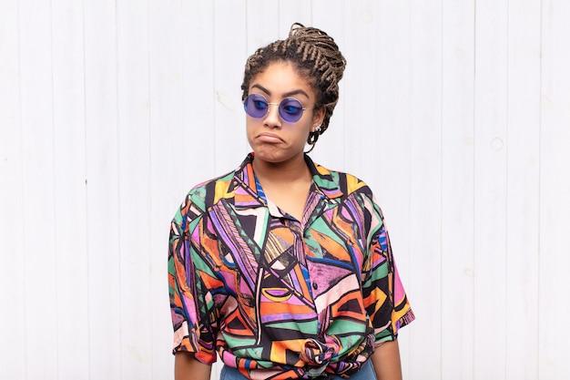 Jovem mulher afro se perguntando, tendo ideias e pensamentos felizes, sonhando acordada, olhando para copiar o espaço ao lado
