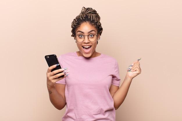 Jovem mulher afro se sentindo chocada, animada e feliz, rindo e comemorando o sucesso, dizendo uau !. conceito de telefone inteligente