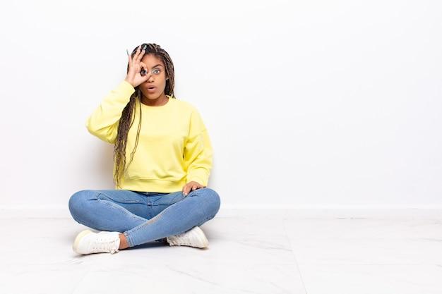 Jovem mulher afro se sentindo chocada, espantada e surpresa