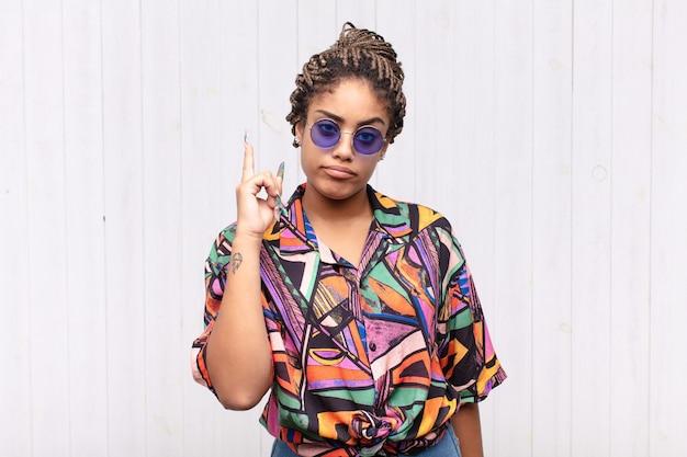 Jovem mulher afro se sentindo como um gênio, segurando o dedo com orgulho no ar depois de realizar uma grande ideia, dizendo eureka