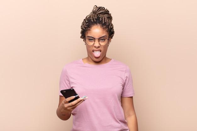 Jovem mulher afro se sentindo enojada e irritada, mostrando a língua, não gostando de algo nojento e nojento. conceito de telefone inteligente