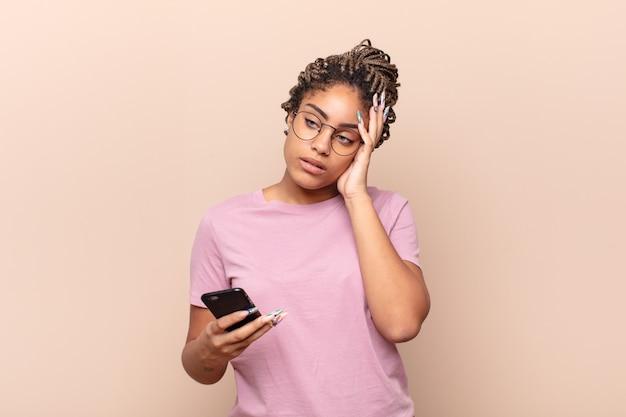 Jovem mulher afro se sentindo entediada, frustrada e com sono depois de uma tarefa cansativa, maçante e tediosa, segurando o rosto com a mão. conceito de telefone inteligente