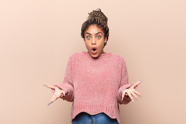 Jovem mulher afro se sentindo extremamente chocada e surpresa