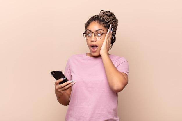 Jovem mulher afro se sentindo feliz, animada e surpresa, olhando para o lado com as duas mãos no rosto