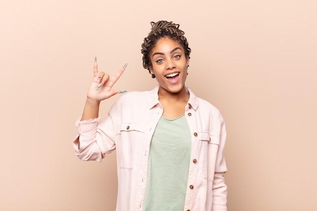 Jovem mulher afro se sentindo feliz, divertida, confiante, positiva e rebelde, fazendo sinal de rock ou heavy metal com a mão