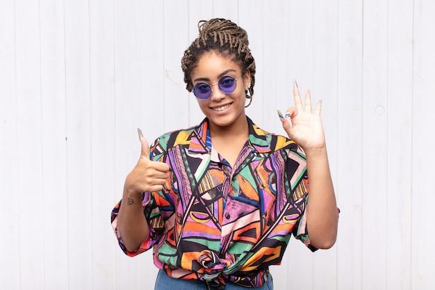 Jovem mulher afro se sentindo feliz, maravilhada, satisfeita e surpresa, mostrando gestos de ok e polegar para cima, sorrindo