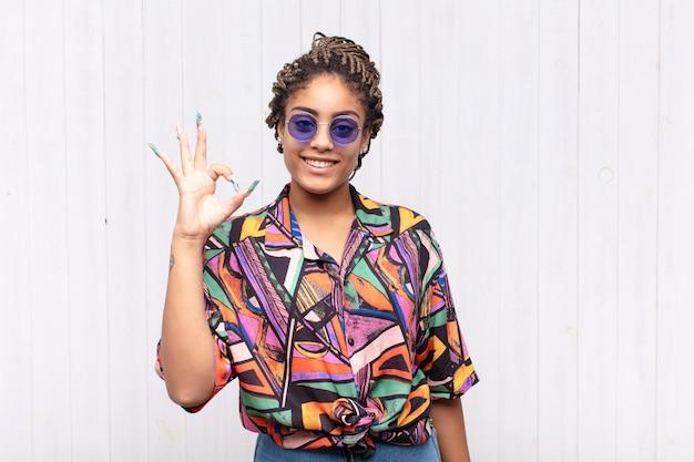 Jovem mulher afro se sentindo feliz, relaxada e satisfeita isolada