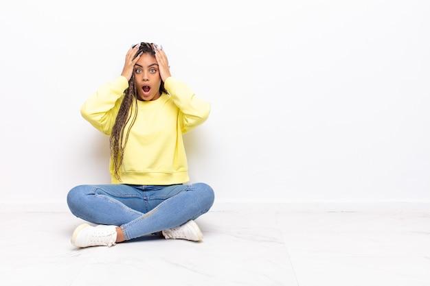 Jovem mulher afro se sentindo horrorizada e chocada, levando as mãos à cabeça