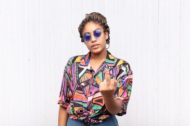 Jovem mulher afro se sentindo irritada, irritada, rebelde e agressiva, sacudindo o dedo do meio e revidando