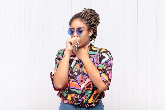 Jovem mulher afro se sentindo mal, com dor de garganta e sintomas de gripe, tosse com a boca coberta