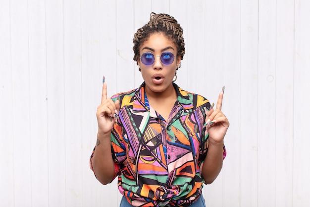 Jovem mulher afro se sentindo maravilhada e de boca aberta apontando para cima com um olhar chocado e surpreso