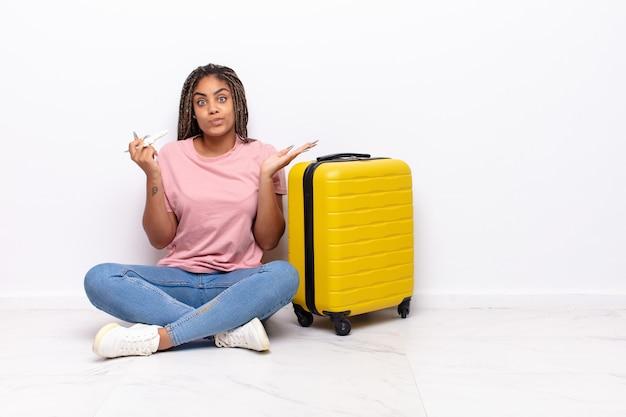 Jovem mulher afro se sentindo perplexa e confusa, duvidando, ponderando ou escolhendo diferentes opções com expressão engraçada