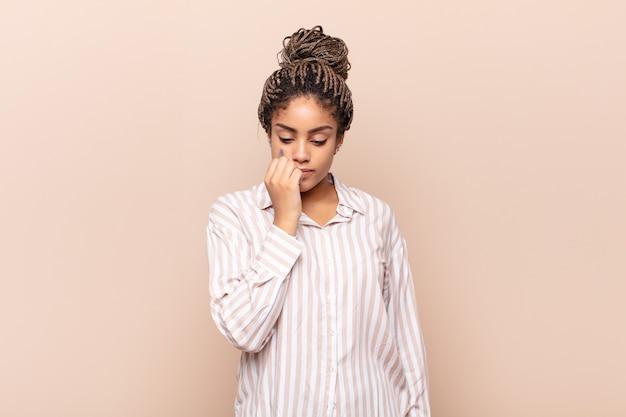 Jovem mulher afro se sentindo séria, pensativa e preocupada, olhando para o lado com a mão pressionada contra o queixo