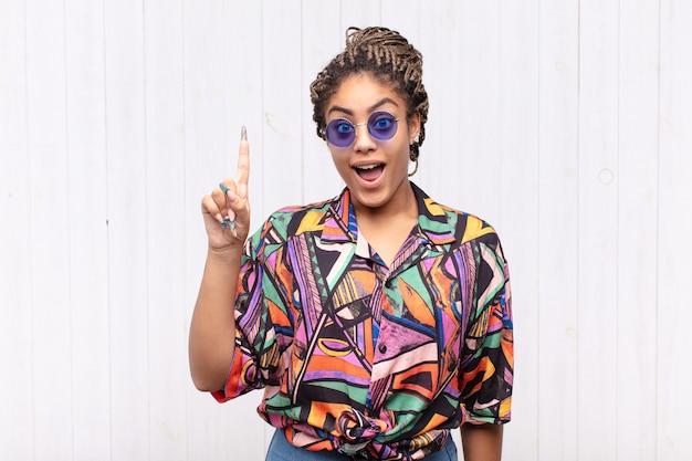 Jovem mulher afro se sentindo um gênio feliz e animado depois de realizar uma ideia, levantando o dedo alegremente, eureka!