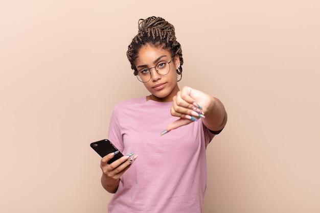 Jovem mulher afro se sentindo zangada, irritada, desapontada ou descontente, mostrando o polegar para baixo