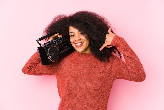 Jovem mulher afro segurando um cassete isolado, mostrando um gesto de chamada de telefone móvel com os dedos.