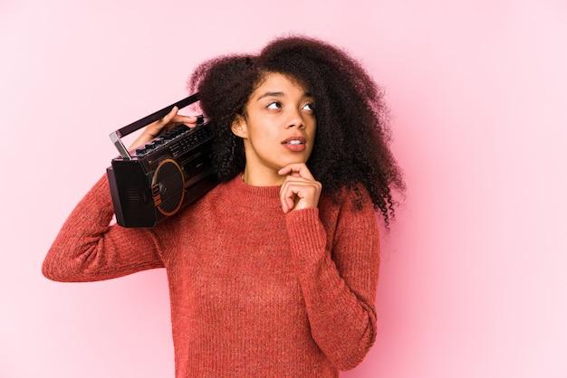 Jovem mulher afro, segurando um cassete, olhando de soslaio com expressão duvidosa e cética.