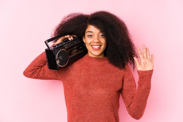 Jovem mulher afro segurando um cassete sorrindo alegre mostrando número cinco com os dedos.