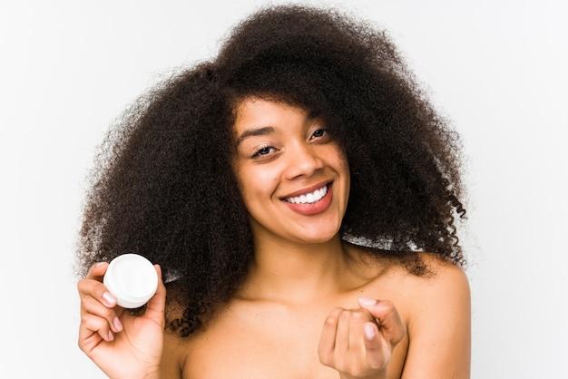 Jovem mulher afro, segurando um hidratante isolado apontando com o dedo para você, como se convidando se aproximar.