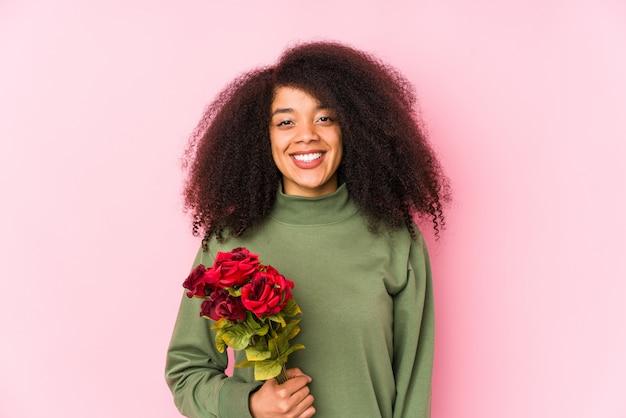 Jovem mulher afro segurando uma rosas