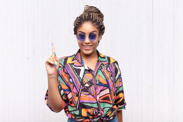 Jovem mulher afro sorrindo alegre e feliz, apontando para cima com uma das mãos para copiar o espaço