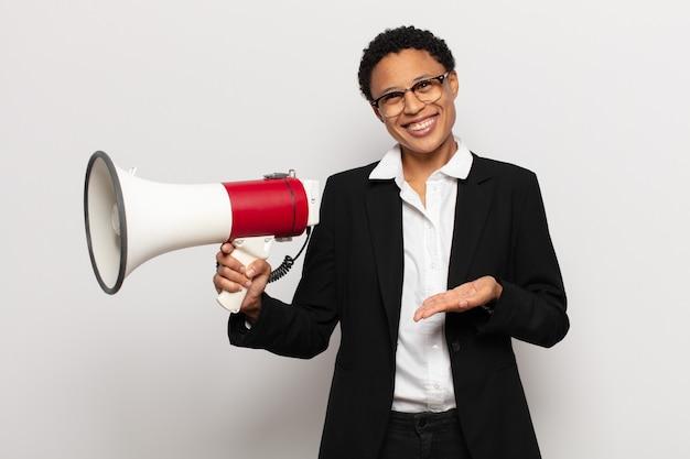 Jovem mulher afro sorrindo alegremente, se sentindo feliz e mostrando um conceito no espaço da cópia com a palma da mão