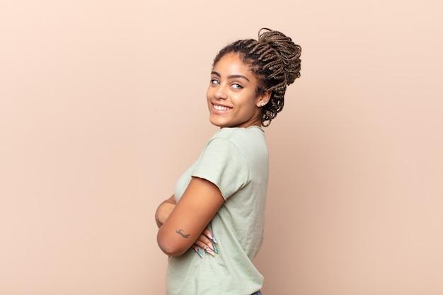 Jovem mulher afro sorrindo alegremente, sentindo-se feliz, satisfeita e relaxada, de braços cruzados e olhando para o lado