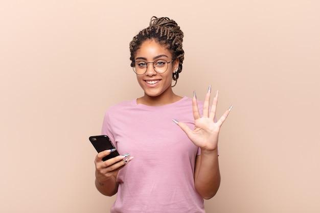 Jovem mulher afro sorrindo e parecendo amigável, mostrando o número cinco ou quinto com a mão para a frente, em contagem regressiva. conceito de telefone inteligente