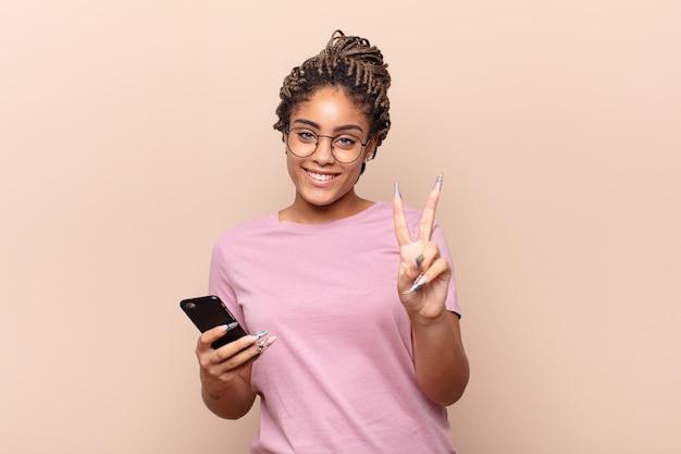 Jovem mulher afro sorrindo e parecendo amigável, mostrando o número dois ou o segundo com a mão em contagem regressiva conceito de telefone inteligente