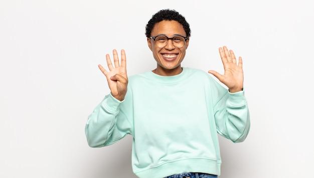 Jovem mulher afro sorrindo e parecendo amigável, mostrando o número nove ou nono com a mão para a frente, em contagem regressiva