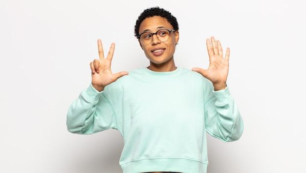 Jovem mulher afro sorrindo e parecendo amigável, mostrando o número oito ou o oitavo com a mão para a frente, em contagem regressiva