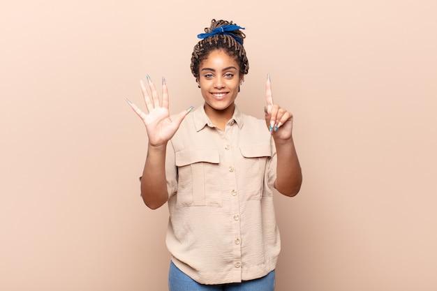 Jovem mulher afro sorrindo e parecendo amigável, mostrando o número seis ou sexto com a mão para a frente, em contagem regressiva
