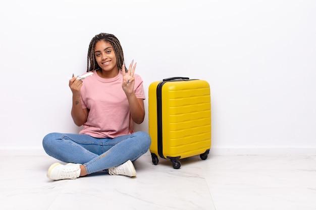 Jovem mulher afro sorrindo e parecendo amigável, mostrando o número três ou terceiro com a mão para a frente, em contagem regressiva. conceito de férias