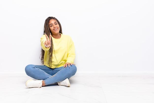 Jovem mulher afro sorrindo e parecendo feliz, despreocupada e positiva, gesticulando vitória ou paz com uma das mãos
