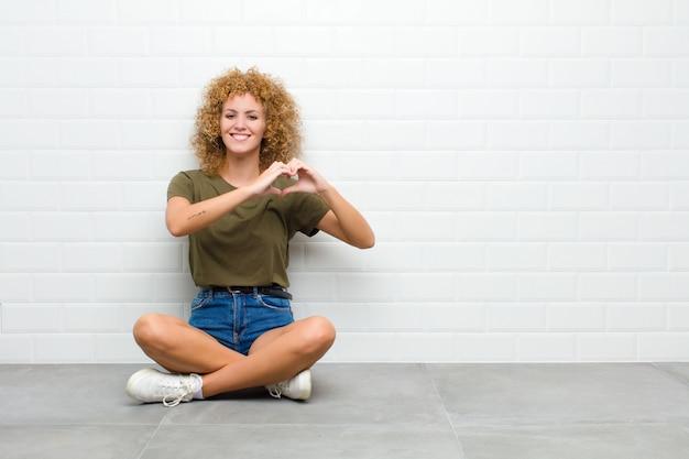 Jovem mulher afro, sorrindo e se sentindo feliz, fofa, romântica e apaixonada, fazendo formato de coração com as duas mãos, sentada no chão