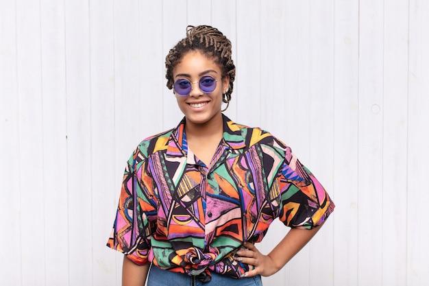 Jovem mulher afro sorrindo feliz com uma mão no quadril e uma atitude confiante, positiva, orgulhosa e amigável