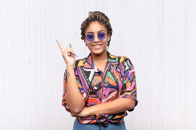 Jovem mulher afro sorrindo feliz e olhando de soslaio, pensando, pensando ou tendo uma ideia