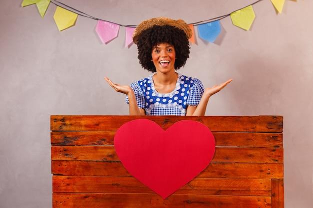 Jovem mulher afro vestida para festa junina atrás de uma placa de madeira com um coração atrás de uma placa de madeira com um coração