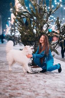 Jovem mulher agachada ao lado de um cachorro em uma rua de inverno