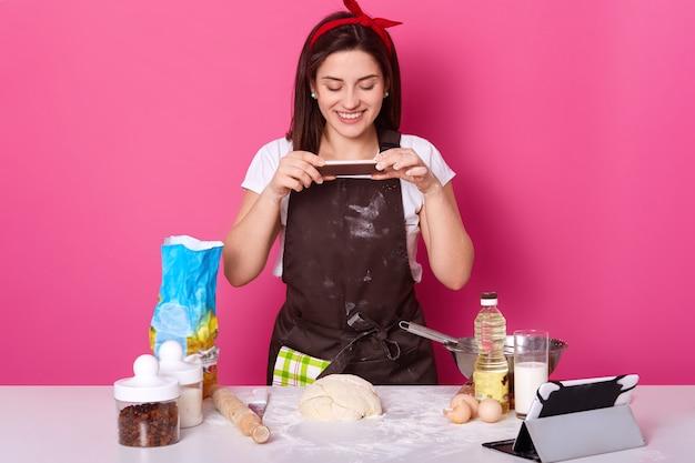 Jovem mulher agradável europeu faz foto de sua torta meio pronta